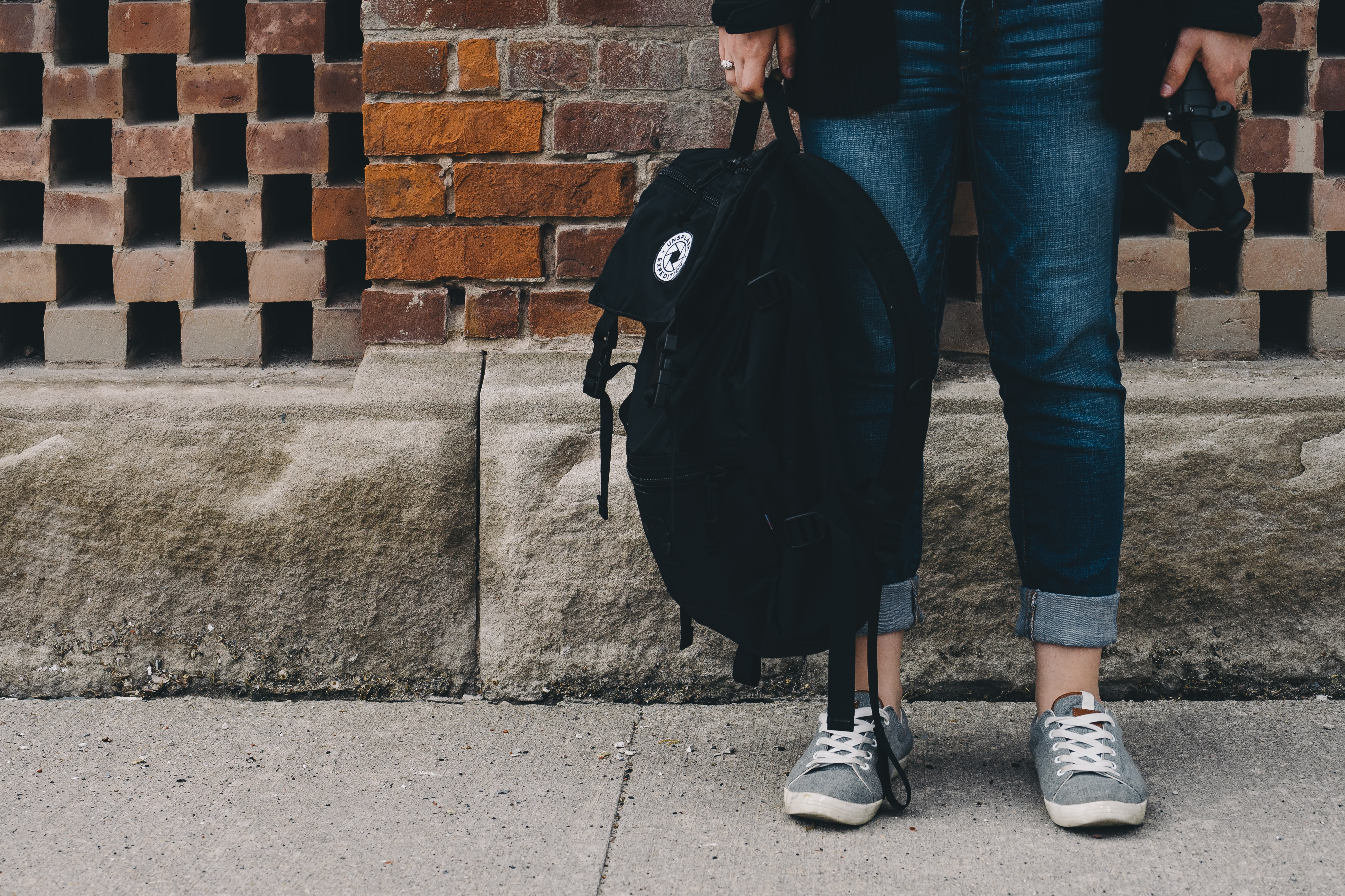 Young person holding a backpack.